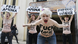 Activists from women's rights group Femen shout slogans during a protest supporting the rights of Arab women, including the Tunisian activist Amina, at the entrance of the Brussels Mosque in Brussels April 4, 2013. REUTERS/Francois Lenoir (BELGIUM - Tags: SOCIETY RELIGION CIVIL UNREST TPX IMAGES OF THE DAY)